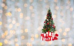 Árbol de navidad con los regalos sobre el muro de cemento imagen de archivo libre de regalías