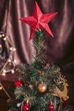 Árbol de navidad con una estrella roja grande y adornado con los juguetes Imagen de archivo libre de regalías