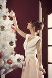 Árbol de navidad de adornamiento femenino precioso Imágenes de archivo libres de regalías