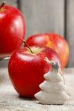 Árbol de navidad de cerámica minúsculo y manzanas rojas grandes Imagen de archivo