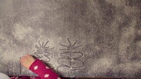 Árbol de navidad del dibujo de la mano de la muchacha en la harina dispersada almacen de metraje de vídeo