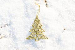 Árbol de Navidad del oro de las decoraciones de la Navidad en al aire libre de tierra de la nieve Imágenes de archivo libres de regalías