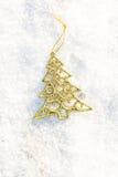 Árbol de Navidad del oro de las decoraciones de la Navidad en al aire libre de tierra de la nieve Imagen de archivo