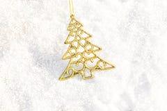 Árbol de Navidad del oro de las decoraciones de la Navidad en al aire libre de tierra de la nieve Foto de archivo libre de regalías