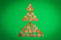 Árbol de navidad de diversas monedas en fondo verde Concepto de la Navidad y del Año Nuevo Ahorros para los días de fiesta fotografía de archivo libre de regalías