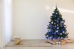 Árbol de navidad el día de la Navidad en un cuarto blanco con los regalos Fotos de archivo