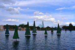 Árbol de navidad en el lago, la montaña rusa y las tiendas coloridas en el cielo nublado en el tema de Seaworld fotografía de archivo