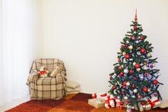 Árbol de navidad en el ` s Eve del Año Nuevo en un cuarto blanco con los regalos de la Navidad Imagen de archivo