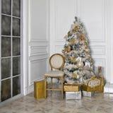 Árbol de navidad en el ` s Eve del Año Nuevo en un cuarto blanco con los regalos de la Navidad Fotografía de archivo libre de regalías