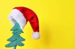 Árbol de navidad en el sombrero de Papá Noel en fondo amarillo Fotografía de archivo