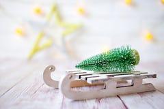 Árbol de navidad en el trineo del juguete Tarjeta de la Navidad y del Año Nuevo en fondo de madera Imágenes de archivo libres de regalías