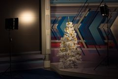 Árbol de navidad en el vídeo del estudio, encendiéndose en ambos lados Árbol de navidad blanco con los juguetes del oro Decoració imagenes de archivo