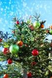 Árbol de navidad en la nieve que cae, ángulo de la elevación con el cielo azul Imagen de archivo
