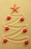 Árbol de navidad en la pintura en arena con las estrellas de mar rojas y las bolas mates rojas de la Navidad Imagen de archivo libre de regalías