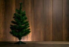 Árbol de Navidad en la tabla de madera con el fondo de madera de la pared, roo de la Navidad Imagen de archivo libre de regalías