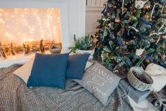 Árbol de navidad en piso de madera en el interiour blanco El árbol de navidad adorna con las flores artificiales, guirnaldas y Foto de archivo libre de regalías