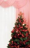 Árbol de navidad en un cuarto al lado de la ventana Foto de archivo