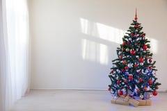 Árbol de navidad en un cuarto blanco para la Navidad con los regalos Imágenes de archivo libres de regalías