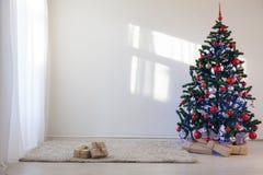 Árbol de navidad en un cuarto blanco para la Navidad con los regalos Imagenes de archivo