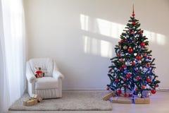 Árbol de navidad en un cuarto blanco para la Navidad con los regalos Foto de archivo