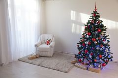 Árbol de navidad en un cuarto blanco para la Navidad con los regalos Foto de archivo libre de regalías