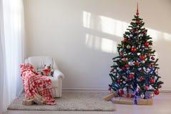 Árbol de navidad en un cuarto blanco para la Navidad con los regalos Imagen de archivo libre de regalías