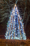 Árbol de navidad encendido coloreado con los ornamentos azules, al aire libre cerca Imagen de archivo