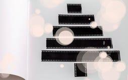 Árbol de navidad estilizado de las tiras de una película en la página blanca de un álbum con los copos de nieve exhaustos Foto de archivo