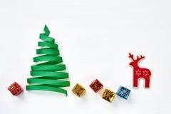Árbol de navidad hecho de cinta verde con la decoración en el fondo blanco Imagenes de archivo