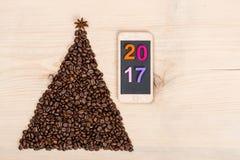 Árbol de navidad hecho de los granos y del teléfono de café en backgr de madera Fotografía de archivo