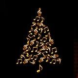 Árbol de navidad hecho de notas musicales de oro brillantes en negro Foto de archivo