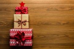 Árbol de navidad hecho de presentes maravillosamente envueltos en fondo de madera Imagenes de archivo