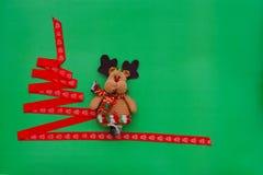 Árbol de navidad hecho de la cinta roja, ciervo en fondo verde Concepto de la Navidad y del Año Nuevo fotos de archivo