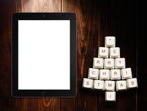 Árbol de navidad hecho de llaves y de la tableta de ordenador en fondo de madera Fotografía de archivo libre de regalías