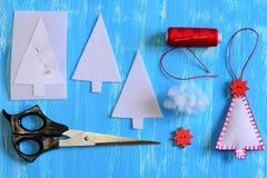 Árbol de navidad hecho a mano del fieltro, plantilla de papel, detalles del fieltro, hilo, aguja, perno, tijeras en un fondo de m Imagen de archivo