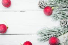 Árbol de navidad de la rama Nevado y cono y bola roja en el fondo de madera blanco del vintage foto de archivo libre de regalías