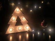 Árbol de navidad de madera con las lámparas Juguetes de la Navidad en la tabla Feliz Navidad fotografía de archivo libre de regalías