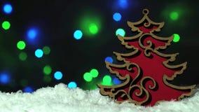 Árbol de navidad de madera rojo de la decoración de la Navidad en la nieve sobre luces blured del bokeh en el fondo metrajes