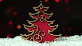 Árbol de navidad de madera rojo de la decoración de Hristmas en la nieve sobre luces blured en el fondo almacen de video