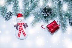 Árbol de navidad natural del verde de la bandera del día de fiesta con el regalo y el muñeco de nieve rojos en un fondo de madera Imágenes de archivo libres de regalías