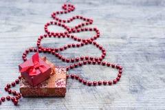 Árbol de navidad rojo con la tarjeta de felicitación de las cajas de regalo Foto de archivo