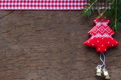 Árbol de navidad rojo en un fondo de madera y ramas de árbol de navidad Imagenes de archivo