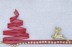 Árbol de navidad rojo de la cinta con el reno de oro y las gotas brillantes Imágenes de archivo libres de regalías