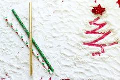 Árbol de navidad rojo pintado en la paja de la nieve y del día de fiesta Imágenes de archivo libres de regalías