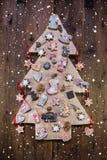 Árbol de navidad tallado hecho a mano adornado con el pan de jengibre, estrellas Fotos de archivo