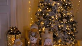 Árbol de navidad, velas, decoraciones y guirnalda que brilla intensamente en sala de estar acogedora metrajes