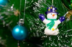 Árbol de navidad verde con las bolas de cristal y el muñeco de nieve coloreados brillantes Fotos de archivo