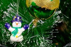 Árbol de navidad verde con las bolas de cristal y el muñeco de nieve coloreados brillantes Foto de archivo