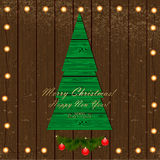 Árbol de navidad verde en el fondo de madera con la guirnalda del li Fotos de archivo