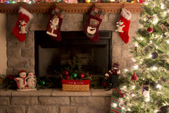 Árbol de navidad y chimenea con las medias de la Navidad Imágenes de archivo libres de regalías